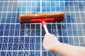 person cleaning solar panels