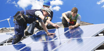 group of men installing solar panels to a roof