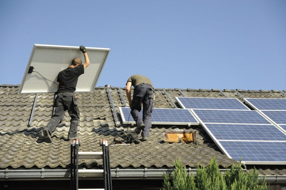 men installing solar panels on a roof