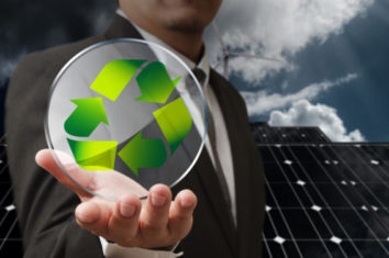 man holding a recycling logo in front of solar panels