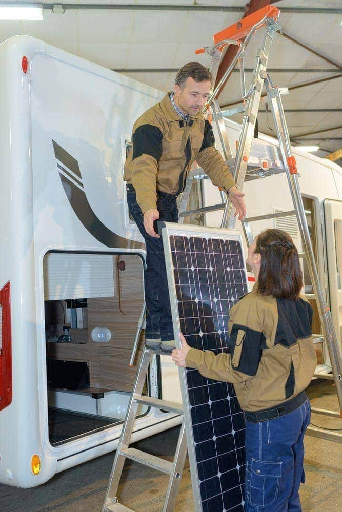 two people installing solar panels kits to an rv