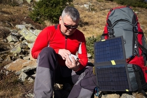 a man checking whether or not the solar charger is charging his phone correctly