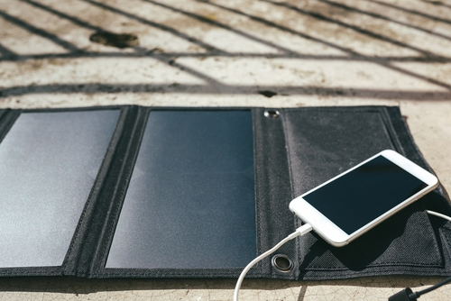 mobile phone charging outside using a solar charger