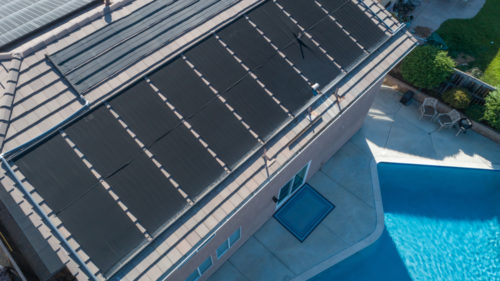 birds eye view of multiple rooftop solar panels and a swimming pool