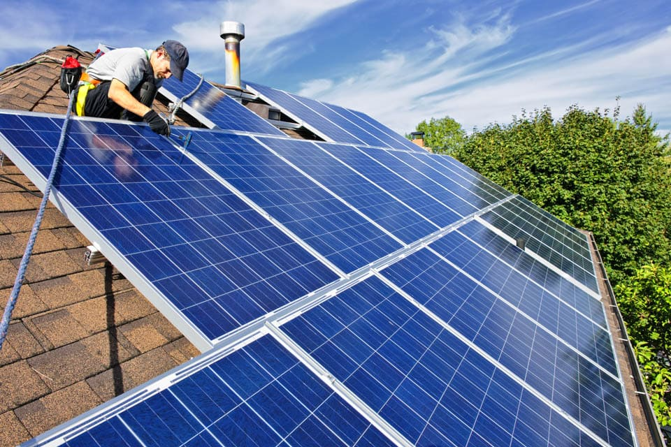 man installing solar panels on a house roof