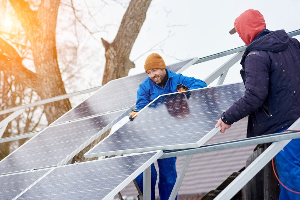 two men putting together solar panels