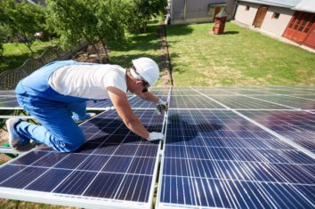 Man on the roof of a house installing brand new solar panels