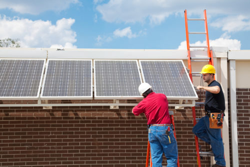 Two men installing solar panels on a large commercial building