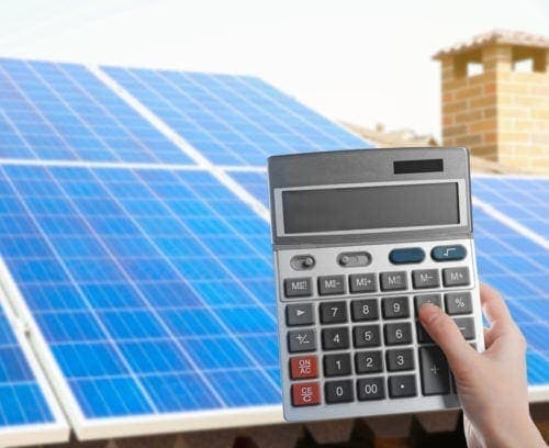 woman calculating how much she saves by using solar panels on her house