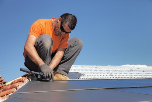 A technician installing solar panels on a roof