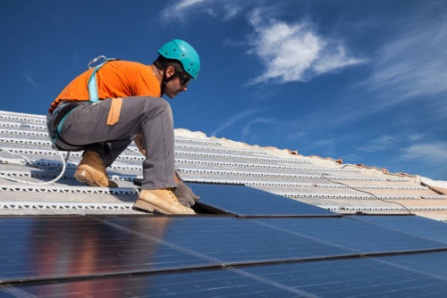 A worker installing a large set of solar panels on a roof