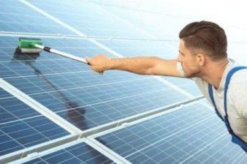 man cleaning his solar panels with a squeegee