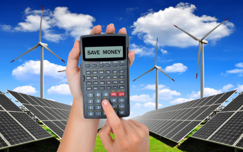 calculator that reads 'save money' being held up in front of solar panels