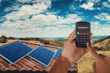 solar panels on a house and a man with a calculator