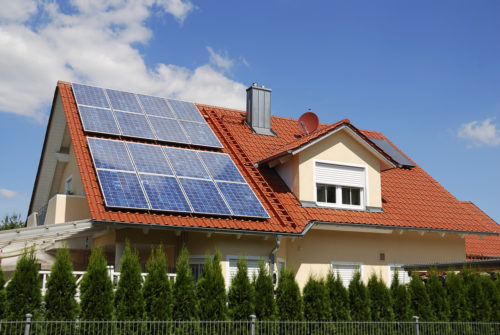 A house with two big sets of solar panels fitted on the roof