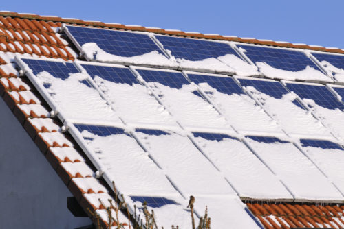 A set of solar panels on a roof that are covered in snow