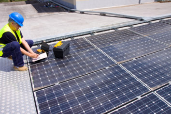 Engineer checking how much energy a set of solar panels are producing