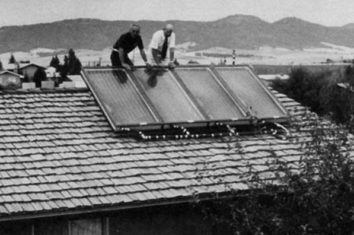 old photograph of two men fixing a solar panel system to a roof