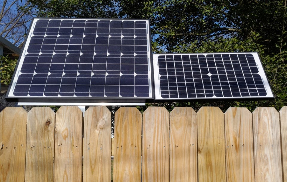 two different sizes of solar panels side by side behind a fence