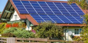 A large set of solar panels installed on the roof of a house