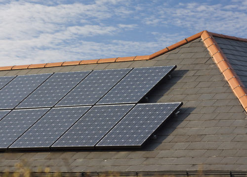 A set of solar panels placed on a roof facing towards the sun