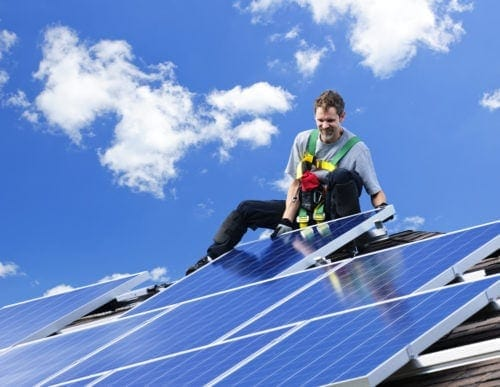 Solar panel installer fitting a set of solar panels on the roof of a home