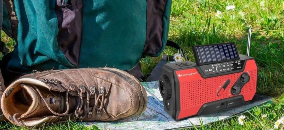 runningsnail solar powered weather radio on the floor next to some camping gear