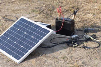 a battery on the ground connected to a portable solar panel