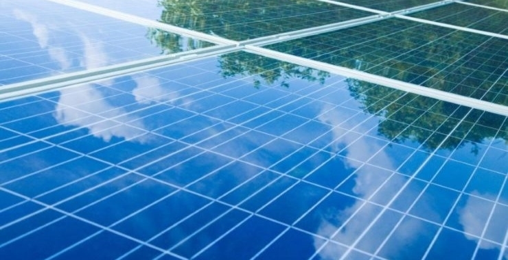 a bright blue set of solar panels with reflection of the sky in them