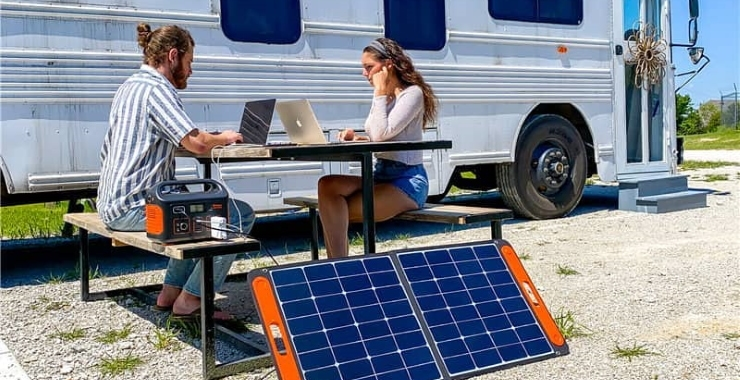 a couple using a solar generator to connect their laptops