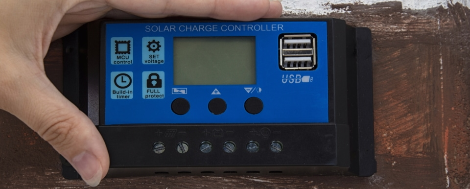 a hand turning on a solar charge controller