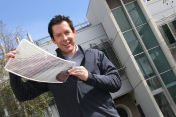 a man holding a printed solar panel