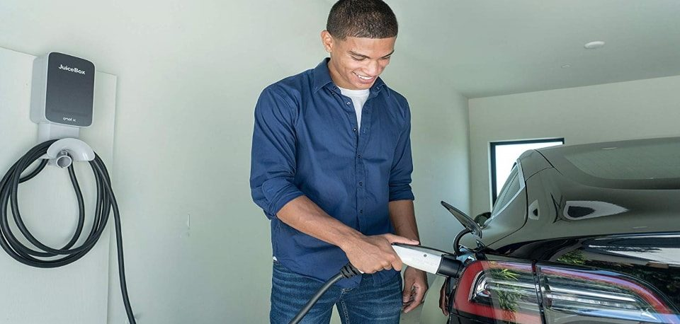 a man using his ev charger at home