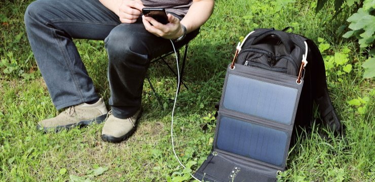 a person charging his cell phone with a portable solar panel