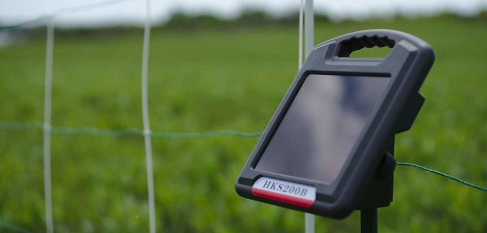 a solar electric fence charger on the grass