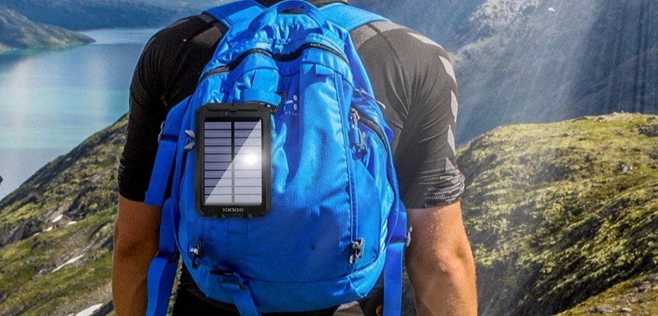 a solar power bank hangs in a man's backpack
