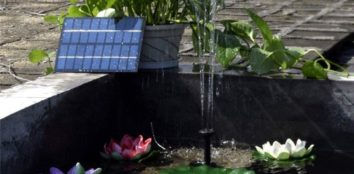 a solar powered water pump working in a small pond