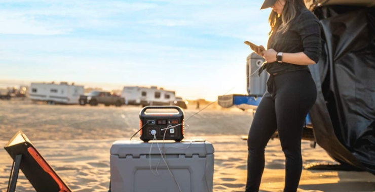 a woman on the beach using a solar generator to charge her phone