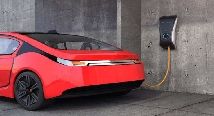 An electric vehicle charging station connected to a red car