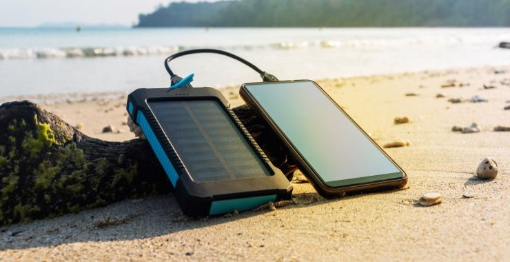 image showing a solar battery charger connected to a mobile phone on the beach
