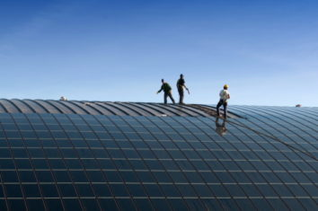 people installing solar panels on the roof of a company