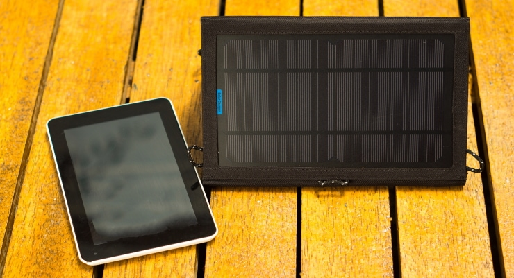 portable solar charger sitting on wooden surface next to tablet