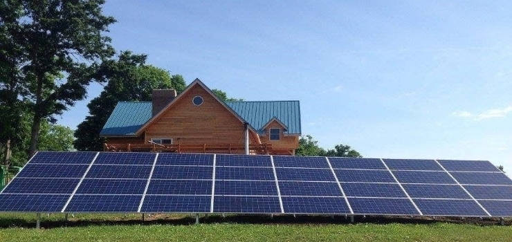 solar panels installed on the grass outside of a house