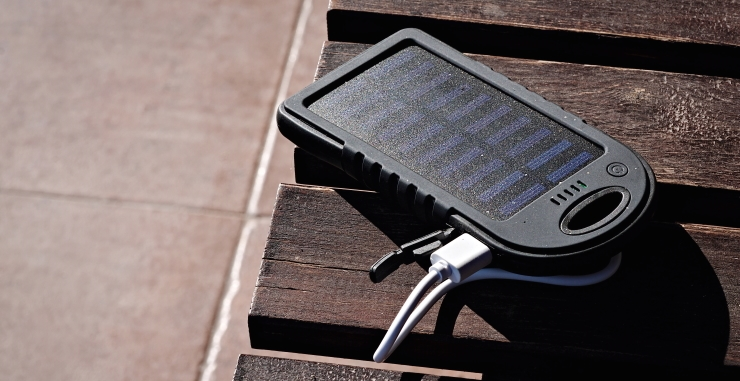 solar powered power bank on wooden table in the sun