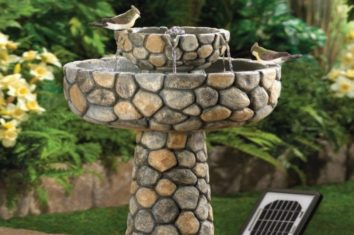 two birds sitting on a solar birdbath fountain