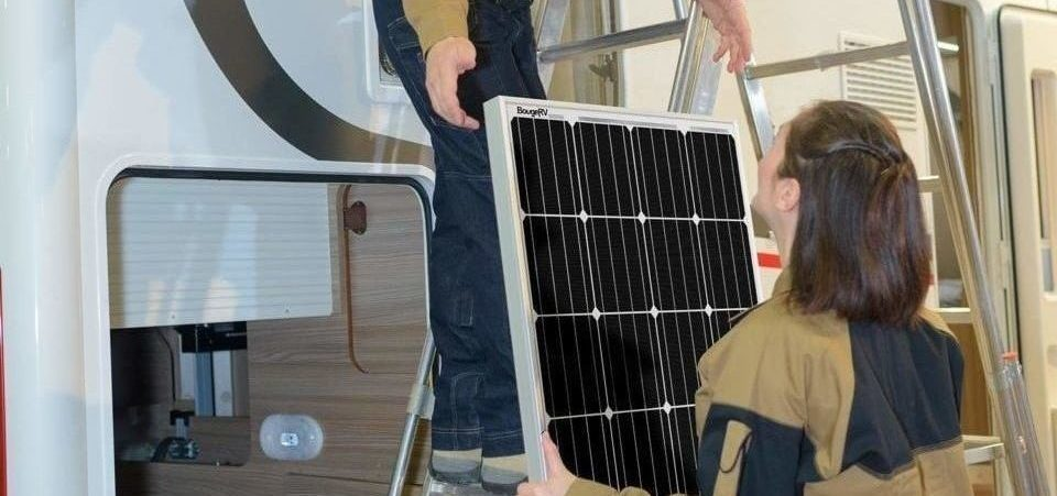 two people installing a solar panel on top of a van