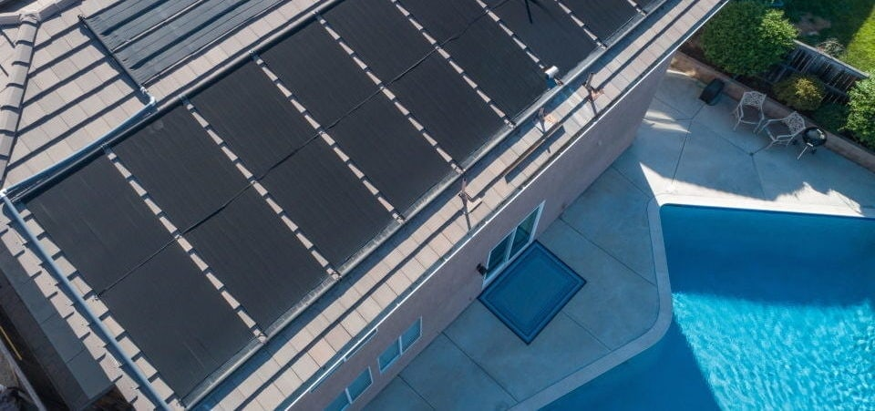 view of rooftop solar panels and a swimming pool