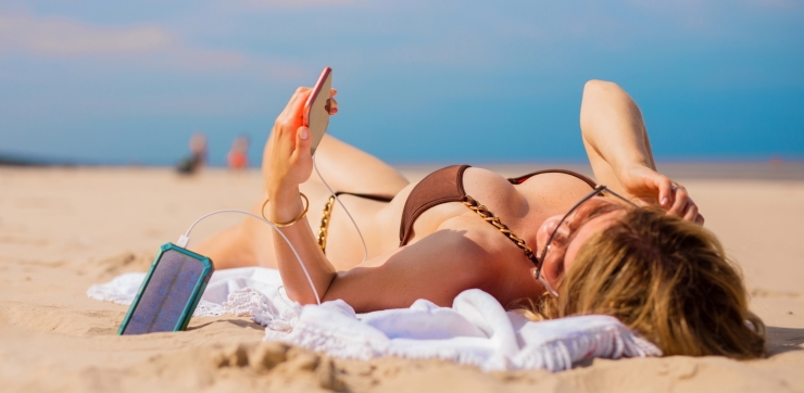 woman charging mobile phone with portable solar power battery bank while lying on the beach
